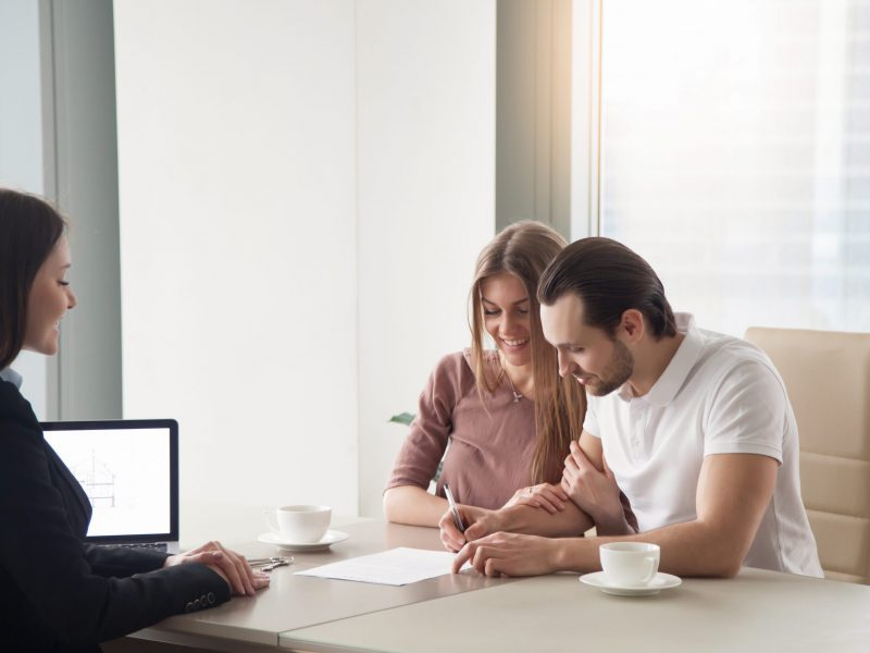 Happy young couple taking real estate purchase loan, signing agreement, rental contract, making investment in property sitting at the office table opposite female realtor or mortgage advisor